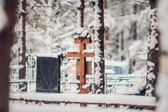 老积雪的花岗岩石头十字架构筑用红色莓果在一个老坟园发现了在冬天 免版税库存照片