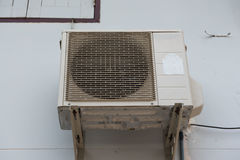 老空气压缩机在墙壁家后位于 免版税库存图片