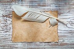 老空白的纸片在葡萄酒木头板的羽毛 库存图片