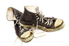 老穿的对在白色背景的老黑白高梆的网球鞋 免版税库存照片