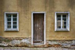 老窗口和门与难看的东西崩裂了墙壁 免版税库存图片