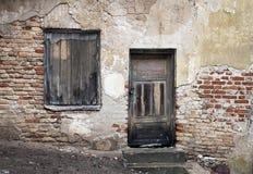 老窗口和门与破裂的墙壁 免版税库存图片