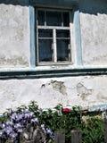 老窗口在有篱芭的一个村庄房子里在窗口和花下 库存照片