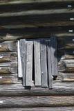 老窗口锤击了一个木房子,一间被放弃的农舍俄罗斯的木板条 中断在村庄,被放弃的settl 免版税库存图片