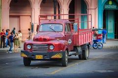 老站立在古巴人有人的哈瓦那街道上的葡萄酒减速火箭的经典平直的卡车看法在背景中 库存照片