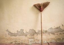 老笤帚和难看的东西水泥墙壁 库存图片