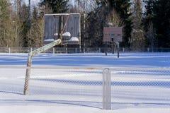 老篮球场在雪的冬天 免版税库存照片