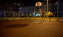 老篮球,橄榄球法院在晚上,在公寓单元的庭院里房子 街道都市背景 库存图片