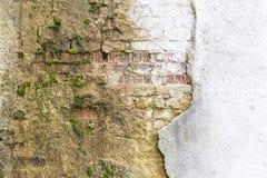 从老红土砖和损坏的膏药框架背景纹理的残破的葡萄酒砌墙壁片段 库存照片