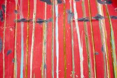 老红色与五颜六色的条纹的被绘的表面 图库摄影
