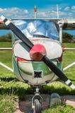 老红色和白色单引擎推进器飞机,正面图,停放在草地 免版税库存图片