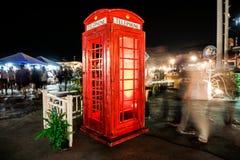 老红色投币式公用电话围拢与人 免版税图库摄影