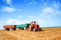 老红色拖拉机和拖车在麦子期间在多云summ收获 库存照片