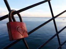 老红色挂锁和在大湖后 库存图片