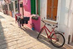 老红色自行车在Burano海岛, V长期停放了外在墙壁 免版税图库摄影
