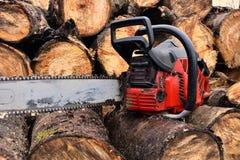 老红色锯和被切开的木柴 免版税库存图片