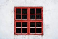 老红色风化了与正方形的窗口在有破旧的纹理的白色墙壁上 免版税库存照片