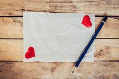 老纸和红色心脏与铅笔在木背景为valen 免版税库存图片