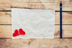老纸和红色心脏与铅笔在木背景为valen 图库摄影