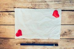 老纸和红色心脏与铅笔在木背景为valen 库存照片