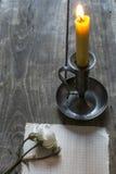 老纸片、桃红色玫瑰和蜡烛在木背景 库存图片