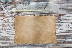 老纸片在葡萄酒木板的羽毛 免版税图库摄影