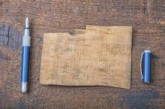 老纸被撕毁的张智慧的消息或词的与笔的在棕色木头 库存照片