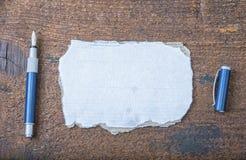 老纸被撕毁的张智慧的消息或词的与笔的在棕色木头 免版税图库摄影