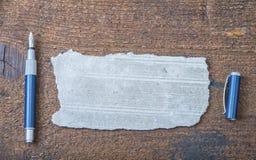 老纸被撕毁的张智慧的消息或词的与笔的在棕色木头 库存图片