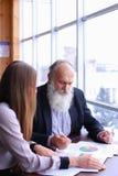 老练的商人退休了微笑并且与ne分享忠告 免版税库存图片