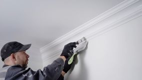 老练的画家上色柱基,固定在天花板和墙壁之间在白色,体力劳动在修理 影视素材