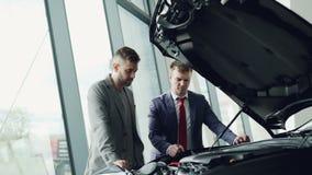 老练的车商显示新的顾客引擎在被打开的帽子下并且告诉他关于质量和特点  影视素材