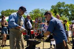 老练的铁匠教一个年轻人的工艺 库存照片