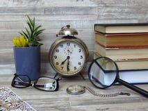 老经典闹钟,怀表,手扶的读书放大器,一副眼镜 时间 眼睛健康&视觉 减速火箭的样式 免版税库存图片