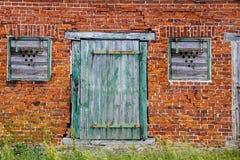 老绿色木破裂的门和窗口在减速火箭的红砖围住门面 免版税库存图片