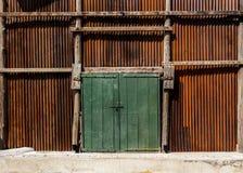 老绿色木门由板条制成在墙壁使锌成波状 库存图片