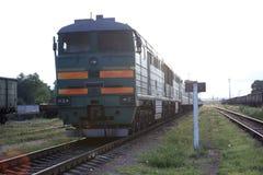 老绿色机车在城市之外的路轨站立 免版税库存照片