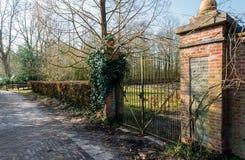 老绿色绘了在两根石工砖柱子之间的门 库存图片