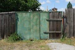老绿色金属门和灰色木篱芭在农村街道上 库存照片
