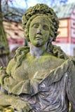 老绿色青苔细节用花花圈包括女孩的雕象 库存照片