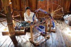 老缅甸妇女是spinnig每莲花螺纹 库存图片