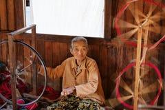 老缅甸妇女松捻大麻制成的绳索用人工 库存照片