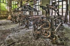 老编织机和转动的机械在一家被放弃的工厂 图库摄影