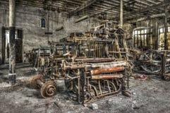 老编织机和转动的机械在一家被放弃的纺织品工厂 图库摄影