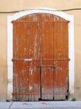 老美丽如画的腐朽的褐色绘了木双门被闩上关闭与在一个白色石框架设置的挂锁 库存照片