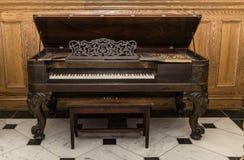 老美丽的华美的站立反对木背景的葡萄酒大平台钢琴 免版税库存图片