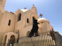老美丽的米黄白色石正统基督教会是祈祷的一个地方对有十字架的上帝和一黑l的雕象 库存照片