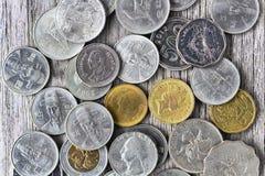 老美国美元硬币、欧元硬币、一1英镑硬币和泰铢在木桌上 主要汇兑的概念能 免版税图库摄影