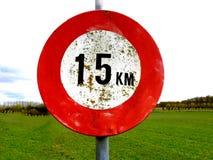 老肮脏的15 km每个小时速度标志有草甸背景 免版税库存照片