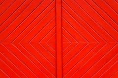 老脏和被风化的红色桔子绘了与形成正方形的对角线的木墙壁板条门细节作为简单饱和 图库摄影
